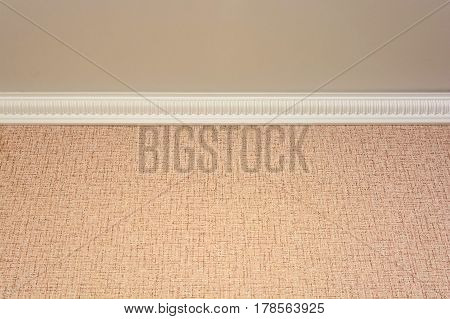Closeup of pink wall and ceiling with white baseboard