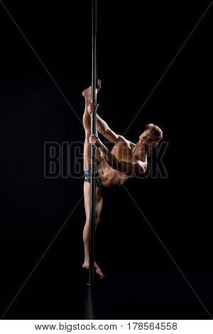 Young fair athletic man exercising on pylon studio shot