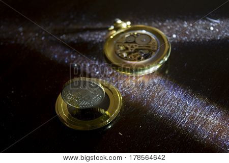 concept of time and money with an ancient watch and a money