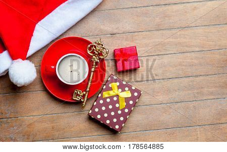 Cup Of Coffee, Gifts, Golden Key And Santa Claus Hat On The Wonderful Brown Wooden Background