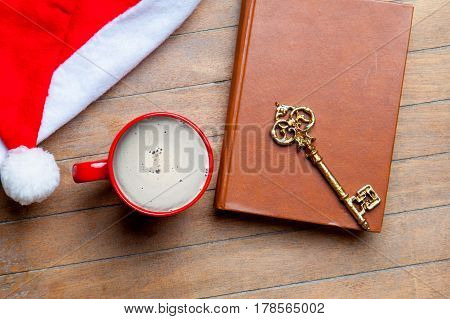 Cup Of Coffee, Golden Key, Book And Santa Claus Hat On The Wonderful Brown Wooden Background