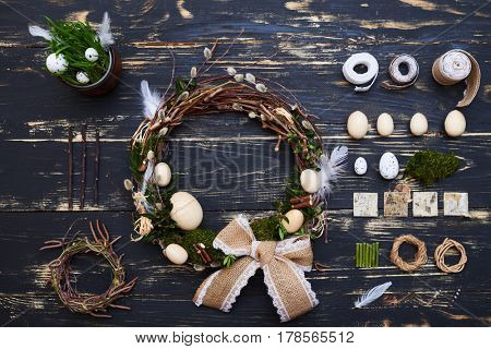 Top view of a table with elements to make a festive wreath for Easter. Tools for decoration and handmade