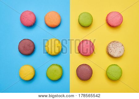 A set of delicious macaroons divided into two parts. Assorted colorful french cookies macaroons