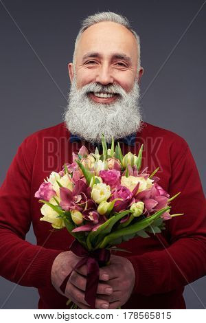 Close-up shot of middle-aged mature man with a bouquet of tulips. Man in red sweater isolated over gray background in the studio