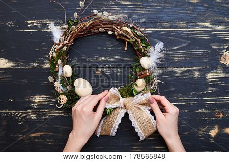 Flat lay picture of hand tying bow on a handmade wreath. Handcraft object. Easter wreath, festive concept
