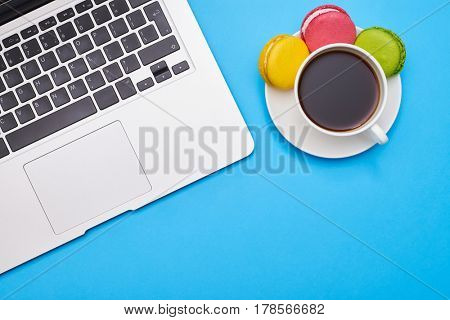 Cropped shot of a workplace with a laptop and coffee with tasty macaroons over blue flatlay. Place for copy space