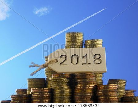 Blue sky with jet going upward as background and  stacks of coin with tag written 2018