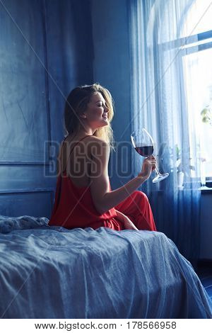 Back view of a young elated woman with glass of red wine sitting on the bed. Woman sitting on the bed in front of the window. Obscure room interior