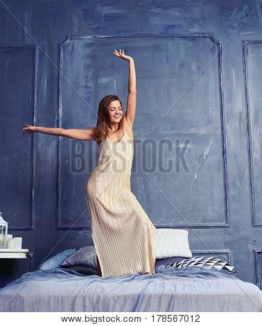 Full-length shot of a merry female in a long nightgown standing with raised hand on the bed. Happy female having fun early in the morning after awakening