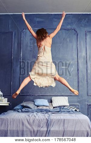 Low angle shot of woman in the air. Back view of a woman in nightgown jumping on bed with arms and legs outstretched