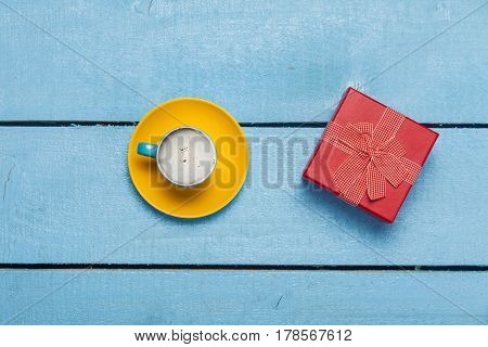 photo of cup of coffee and cute gift on the wonderful blue wooden background