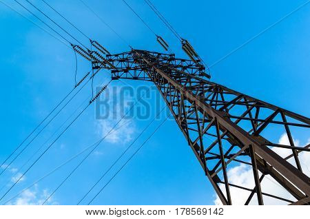 Power transmission tower against the blue sky. Alone pole power lines