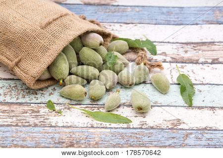 Unripe almonds in bag on vintage table front view