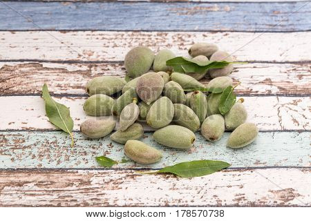 Unripe fresh almonds on vintage table side view