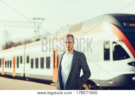 Stylish young man in a coat stands near a modern train