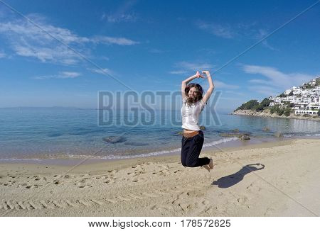 Girl jumping in the shore of a beach