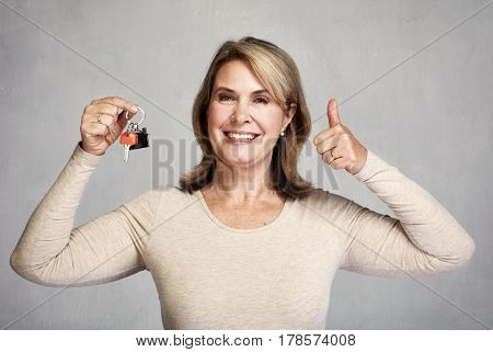 Senior realtor woman with key.