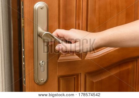 Close-up photo of hands opening door with key