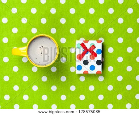 Photo Of Cup Of Coffee And Cute Gift On The Wonderful Green Dotted Background