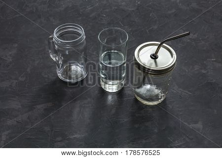 Detox, juice diet. Empty glass jars of different sizes on dark background, set of cans for drinks and juices, top view