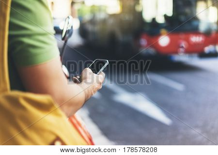 Man pointing on screen smartphone on background red bus tourist hipster waiting taxi and using in hands mobile phone traveler connect wifi internet headlights auto on backdrop city street mockup station