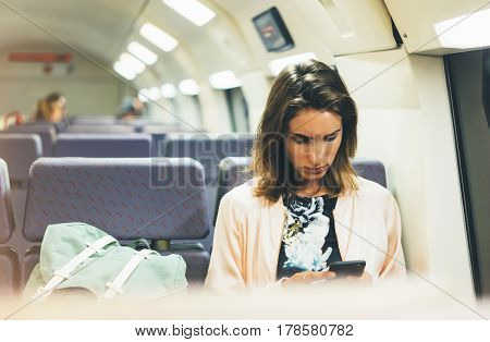 Enjoying travel. Young pretty woman traveling by train sitting near the window using smartphone and looking map in nigth. Tourist texting online message and plan route of railway railroad transport concept