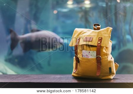 Hipster yellow backpack and map closeup. View from front tourist traveler bag on background blue sea aquarium. Person hiker visiting oceanarium museum in Barcelona on backdrop blank blurred mockup