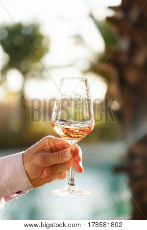 Swirling Glass Of Rose Wine At Wine Tasting. Concept Of Rose Wine
