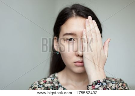 Sad Asian girl covers half of her face with hand. A sad look on her face.