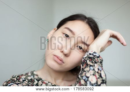 Asian girl with sad eyes tiredly put her head on the palm of your hand