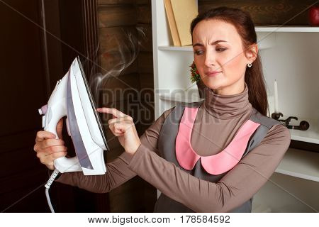 Woman in uniform touches iron hot soleplate