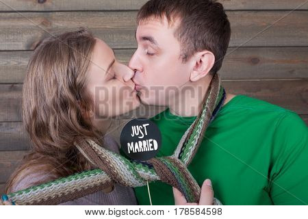 Love couple kisses wrapped in a scarf