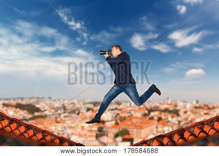 Male photographer jumping on the roofs of houses