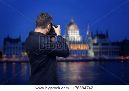 Photographer takes pictures of palace on the river