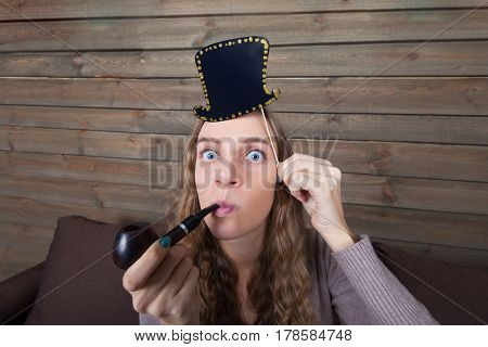 Woman with funny hat on a stick and pipe in hand