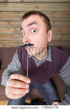 Young man with funny moustache on a stick