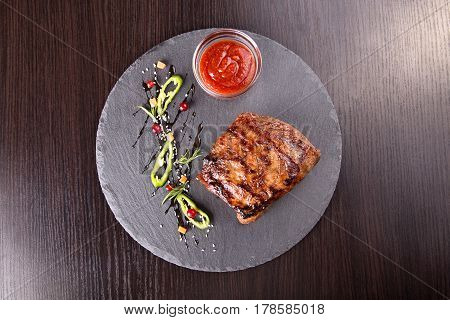 Steak on slate board. standing next to a gravy boat with ketchup. on the board is hot pepper diced carrots red currants sesame. view from above