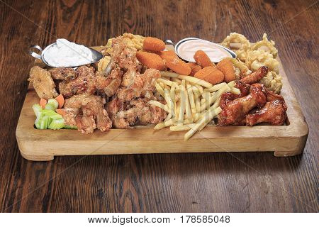 wooden board on a table with assorted fried appetizers: BBQ wings fried squid rings fries grilled cheese sauce