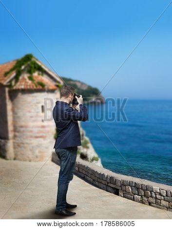 Male photographer taking picture of sea coast