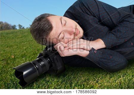 Male photographer with camera sleeping on meadow