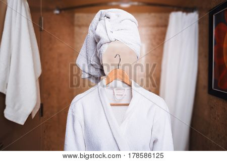 Woman with invisible face in bathrobe and hanger