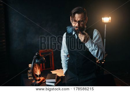 Serious bearded writer in glasses smoking a pipe