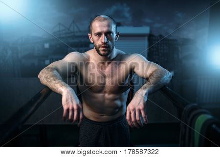 Strong athlete on gymnastic bars in gym