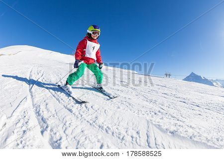 Happy little skier in safety helmet and mask hitting the slope in alpine resort