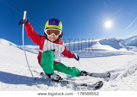 Portrait of smiling kid boy with skis, poles and safety helmet having fun at sunny snowy day
