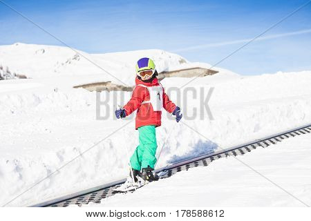 Happy kid boy with skis, poles and safety helmet going uphill using a draglift in snowy mountains
