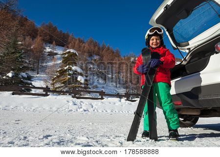 Portrait of cute boy in safety helmet and mask standing next to open car trunk with skis