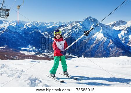 Happy little skier going uphill at the surface ski lift against the beautiful mountains
