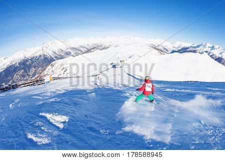 Picture of little skier hitting down the slope on ski race against beautiful mountain scene