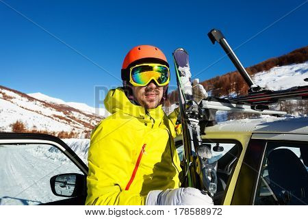 Active man unloading skis from car roof, ready to start skiing at beautiful mountains